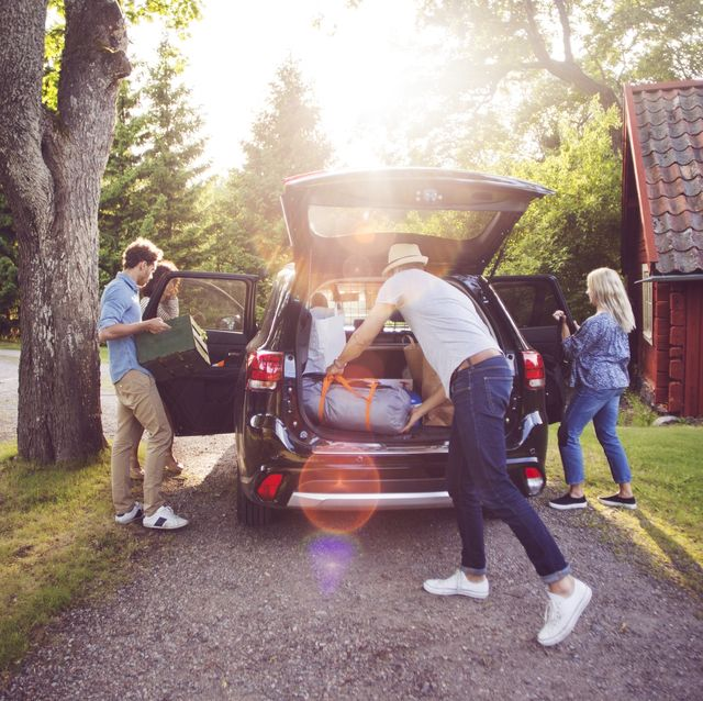 amigos guardando bolsas de viaje en el maletero del coche