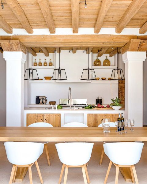 cocina con mesa de comedor de madera alargada y sillas blancas