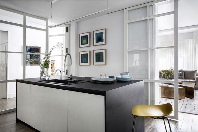 una casa que alcanza la luz  cocina con isla en blanco y negro