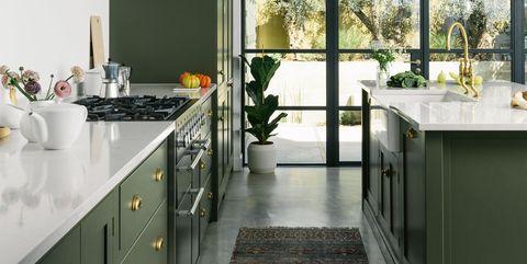 Cocina abierta decorada con armarios de color verde oliva y apliques dorados