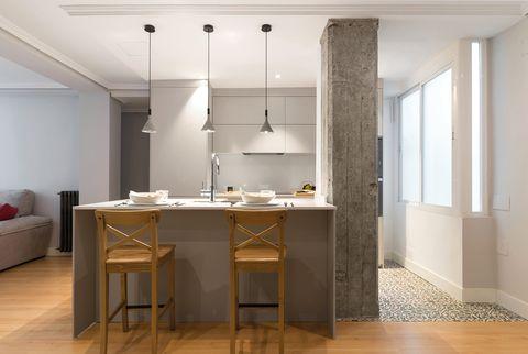 cocina con isla central de diseño moderno en gris abierta al salón