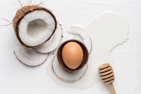 Coconut, egg and fresh milk on a white background, top view
