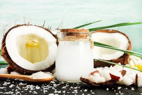 coconut milk glass jar with nuts and oil bottles, fresh coconut flakes