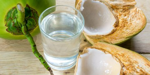 coconut water and fresh coconut on wooden background