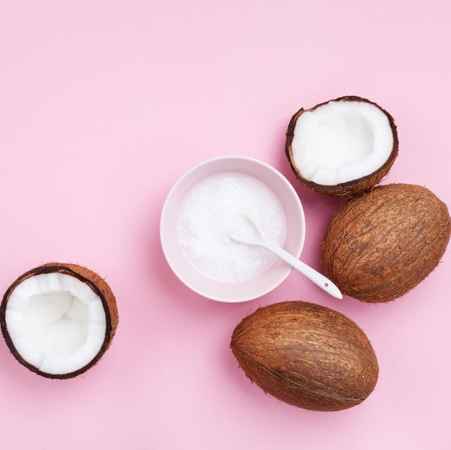 coconuts and coconut oil on pink background
