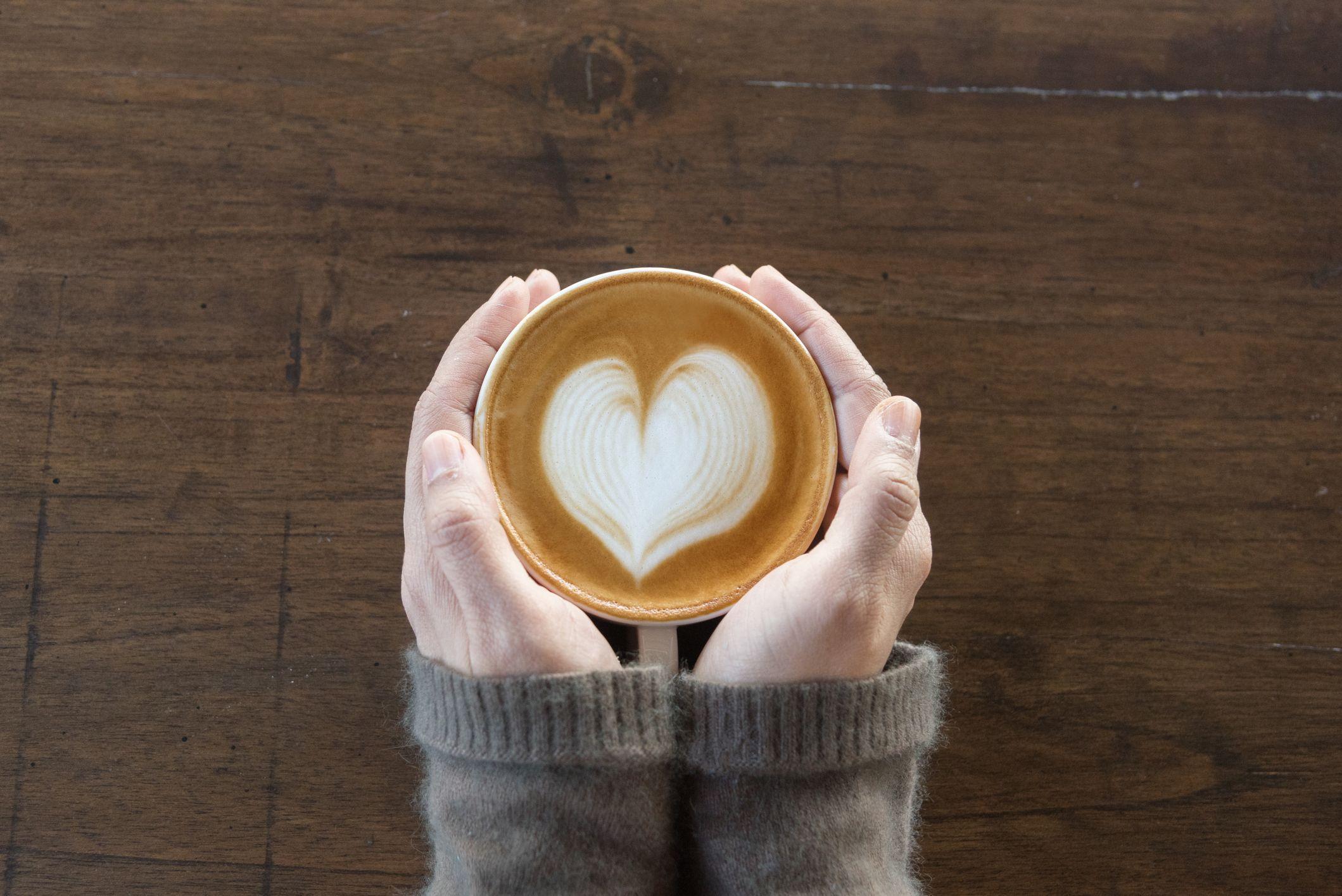 kaffekopp i kaffebutikk kvinnelige hender som holder kopp kaffe på trebordbakgrunn