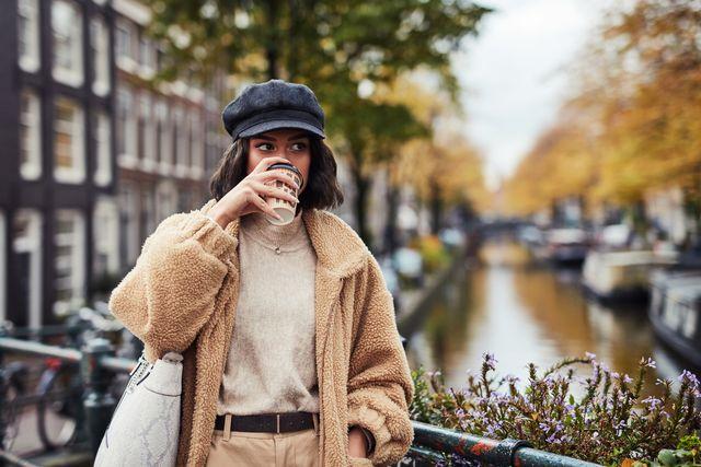 vrouw drinkt op de gracht in amsterdam een koffie