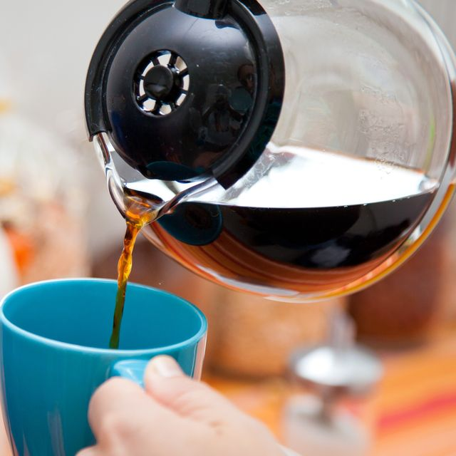 woman pouring coffee pot into a coffee mug in the kitchen