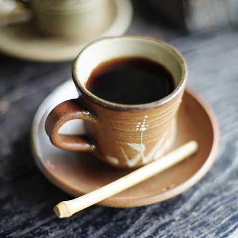 Coffee on the table with little bamboo stirrer