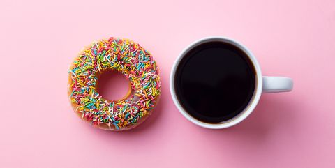 Coffee with donut on pink paper background. Top view. Copy space.