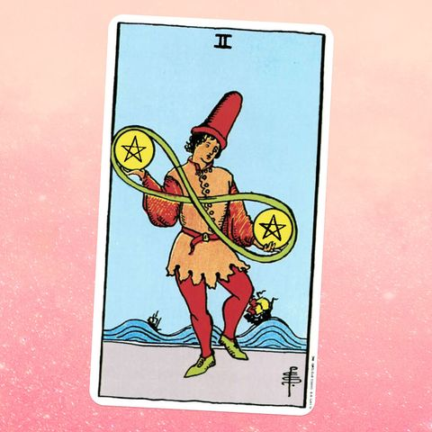 the tarot card the two of coins, showing a perosn in a short tunic and big hat holding two giant coins with a pentacle carved into them, one in each hand