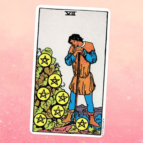 the tarot card the seven of coins, showing a man leaning on a walking stick, a pile of seven coins emblazoned with stars next to him