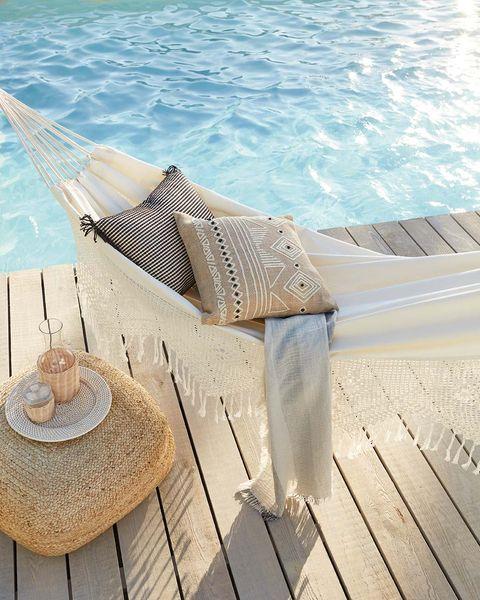 hamaca color blanca y con bordado junto a la piscina estilo boho chic