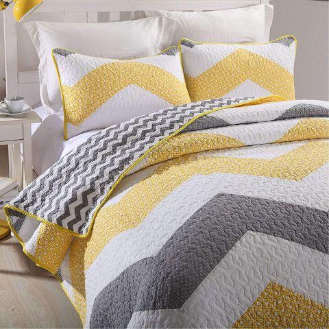 Colcha y almohadas en amarillo y gris