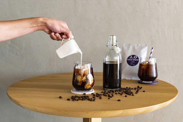 水出しコーヒーのカップににミルクを注ぐ