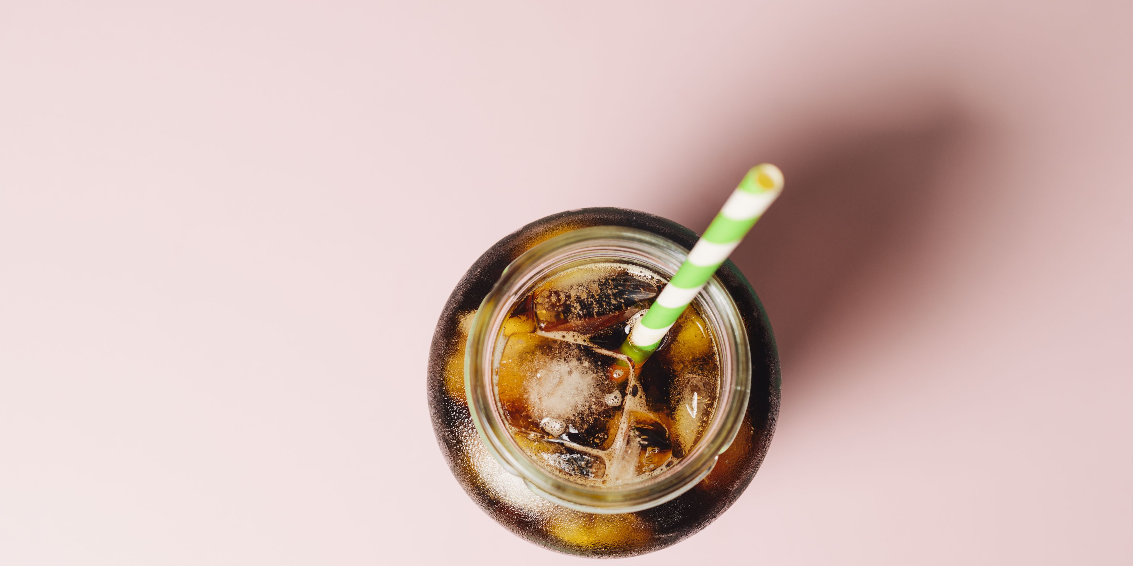 Cold brew coffee against a pink background.