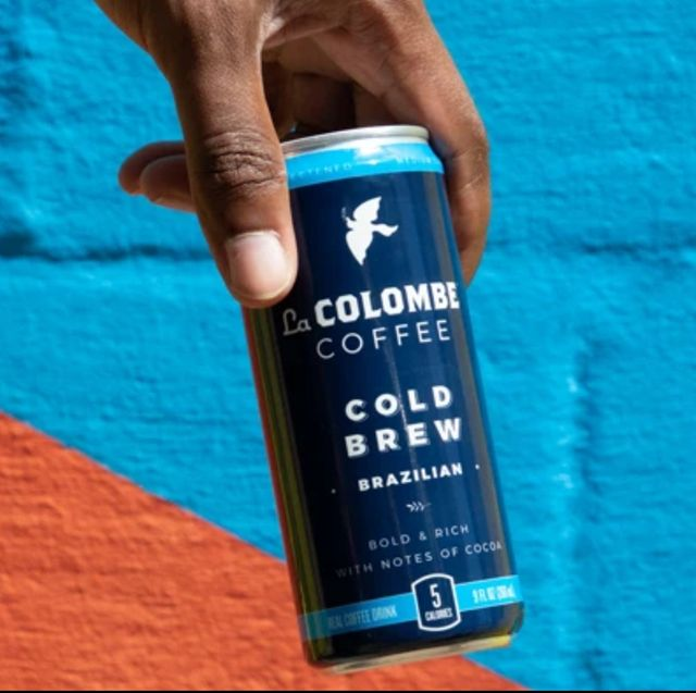 hand holdingcan of La Colombe cold brew coffee against a colorful wall