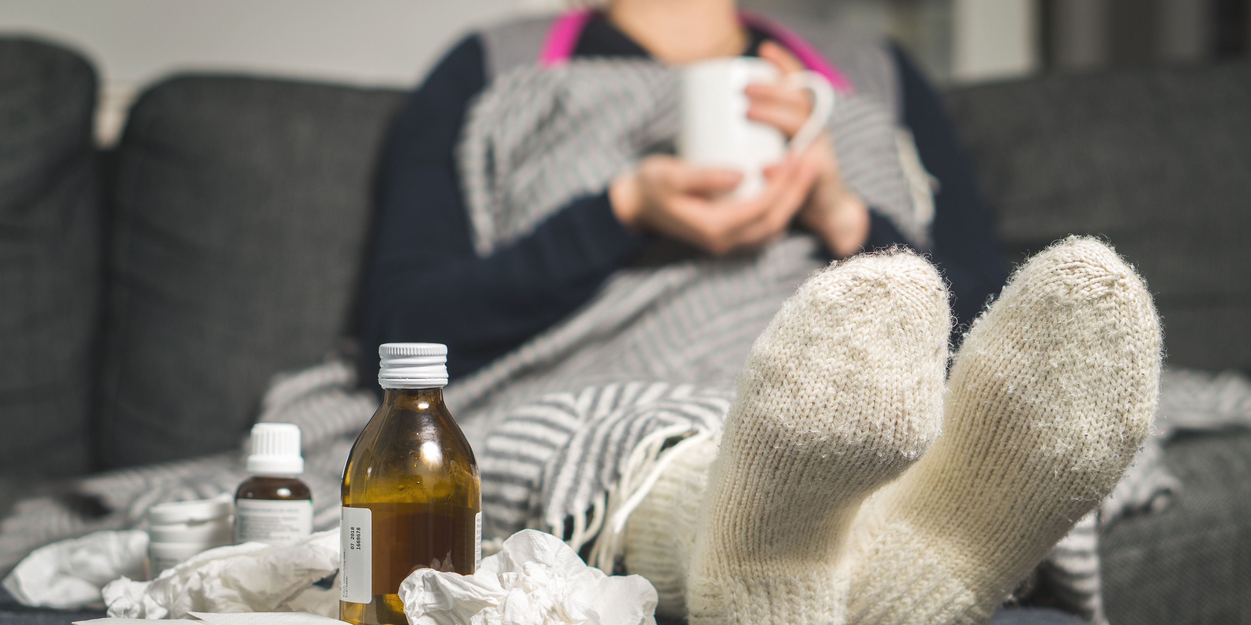 Cold medicine and sick woman drinking hot beverage to get well from flu, fever and virus. Dirty paper towels and tissues on table. Ill person wearing warm woolen stocking socks in winter.