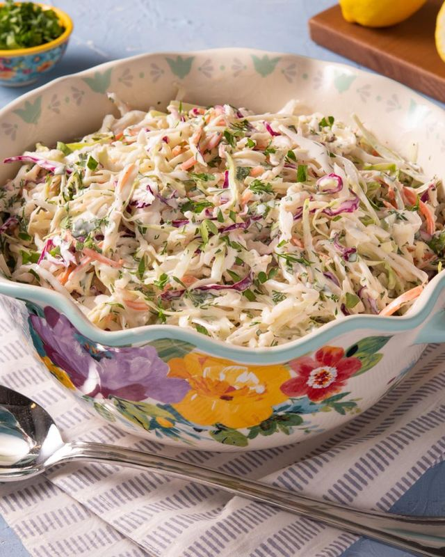 coleslaw in pw bowl with spoon and lemons in back