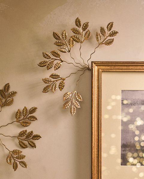 colgador metálico con forma de hojas doradas