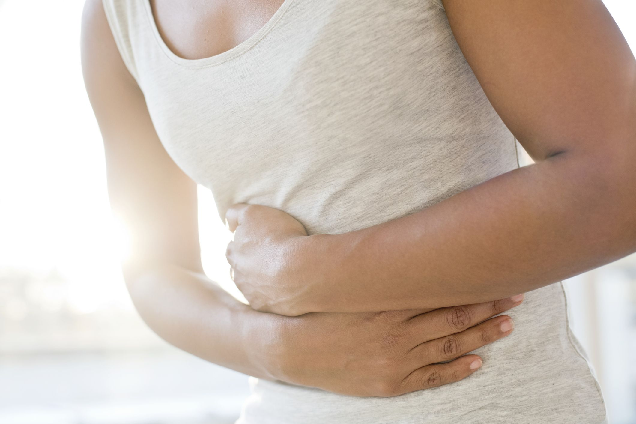 Woman in gray tank top clutching stomach in pain.