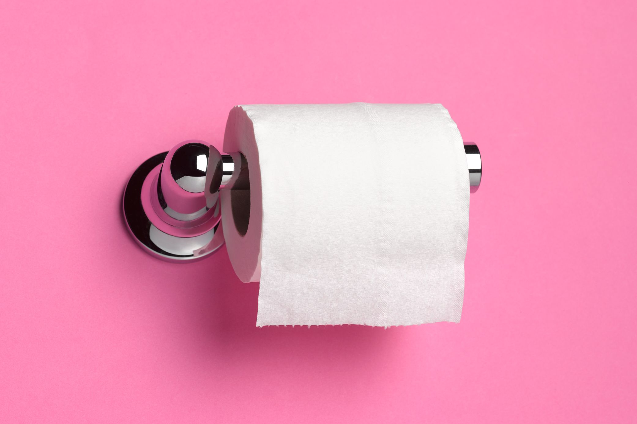 Roll of toilet paper on dispenser in front of pink bathroom wall.