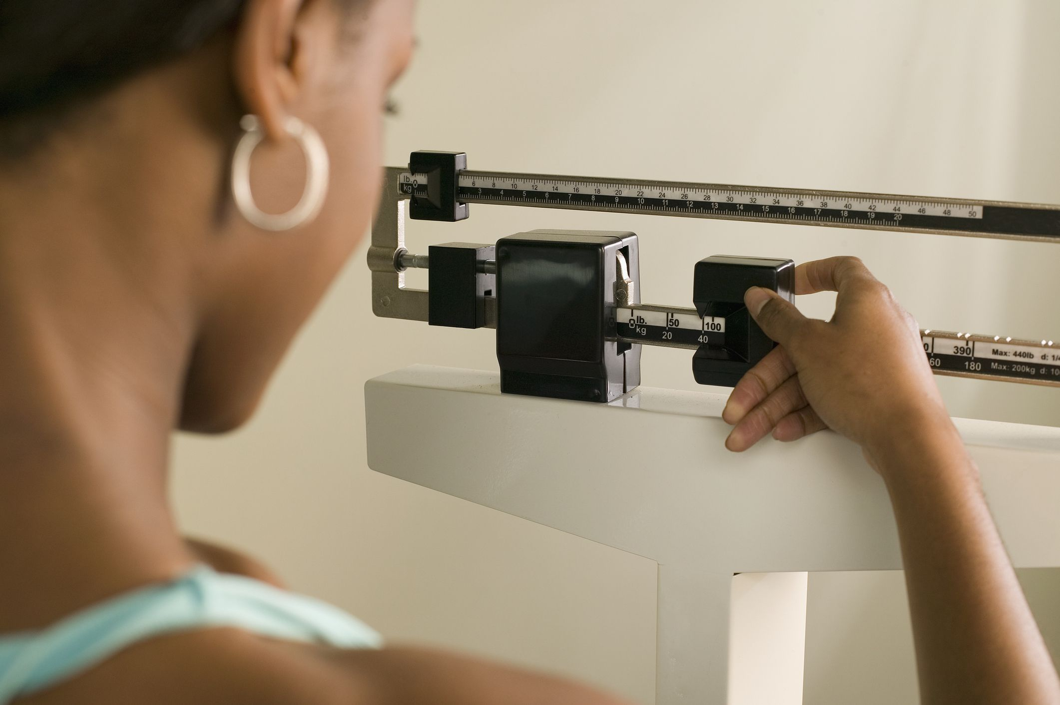 Woman on scale adjusting weight for accuracy.