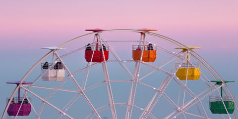 colorful ferris wheel in the tibidabo amusement park mountain with the barcelona city view and the pink sunset sky