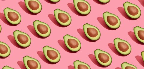 Colorful fruit pattern of fresh cutted avocado halves with pits on coral pink background, top view