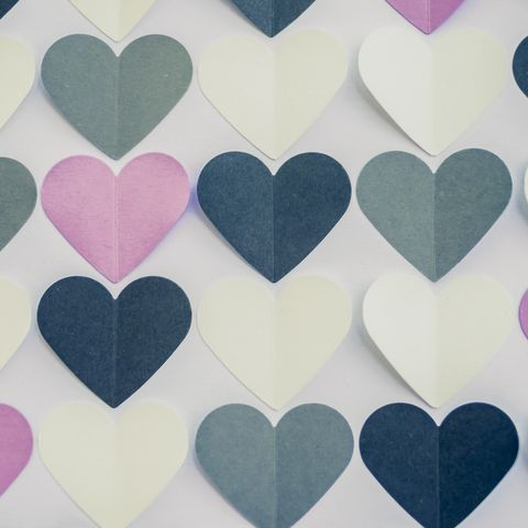 Colorful heart shaped papers on white background.