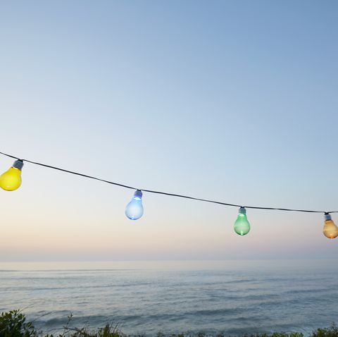 Colorful string lights for party decoration against sea and sky during sunset