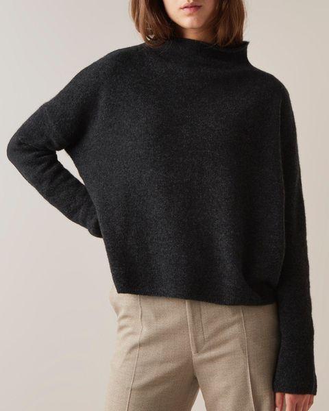 Vrouw met grijze trui van de bijenkorf