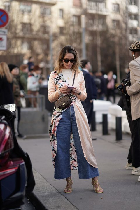 paris, france   february 28 a guest wears hairpins, sunglasses, pearl earrings, a white top, a flowing beige coat with a colorful floral print side, a brown alligator pattern wandler bag, jeans, yellow sandals, outside chloe, during paris fashion week womenswear fallwinter 20192020, on february 28, 2019 in paris, france photo by edward berthelotgetty images