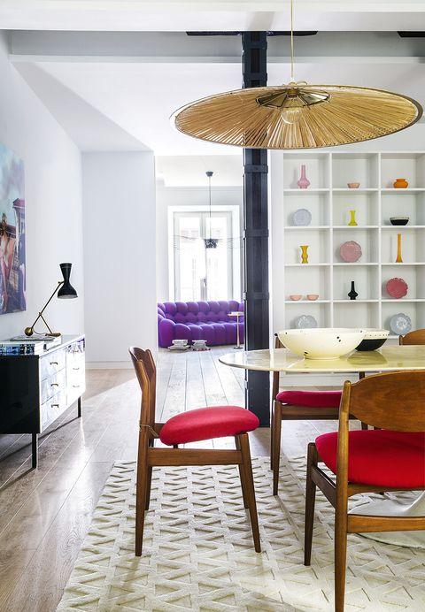 comedor con mesa de mármol, sillas tapizadas y lámparas de rafia