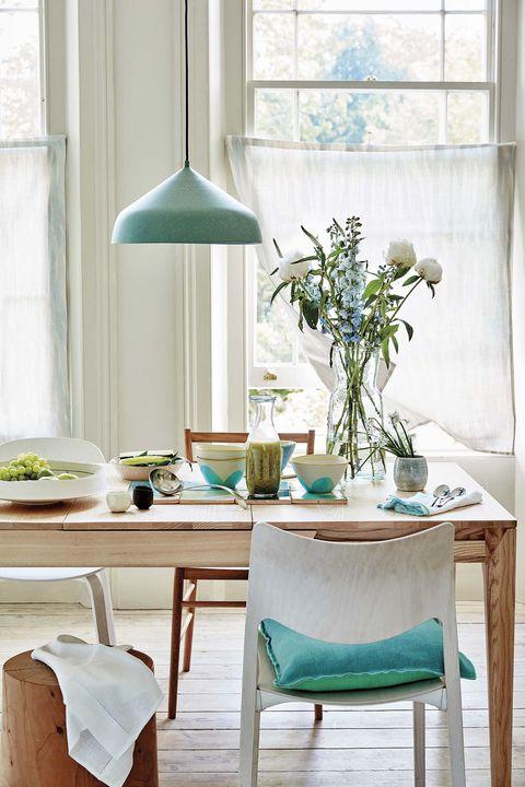 comedor con mesa de madera y lámpara de techo verde