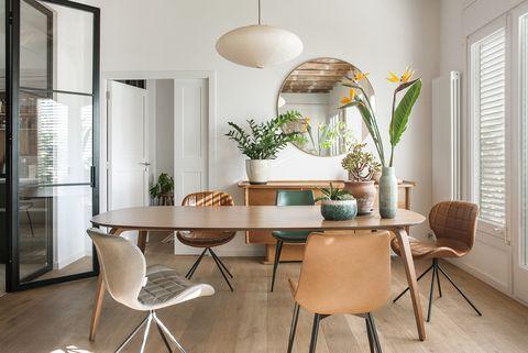 una casa decorada con esencia boho  comedor con mesa ovalada y aparador mid century
