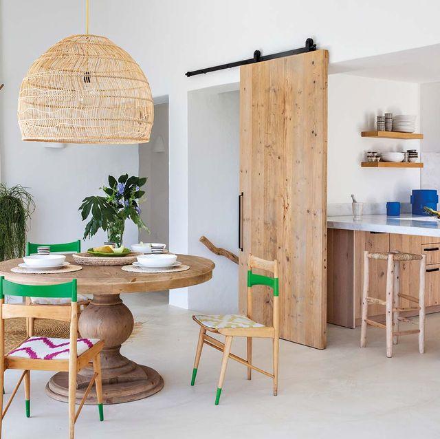 la puerta, en madera de encofrado reciclada, separa las dos plantas de la vivienda
