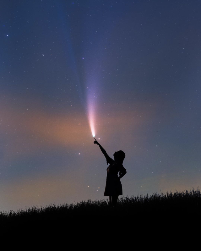 girl pointing to comet in sky