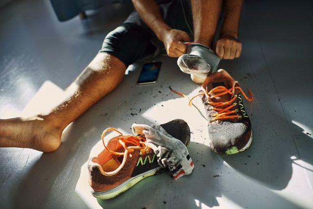 un hombre sentado en el suelo se pone unos calcetines y unas zapatillas antes de salir a correr