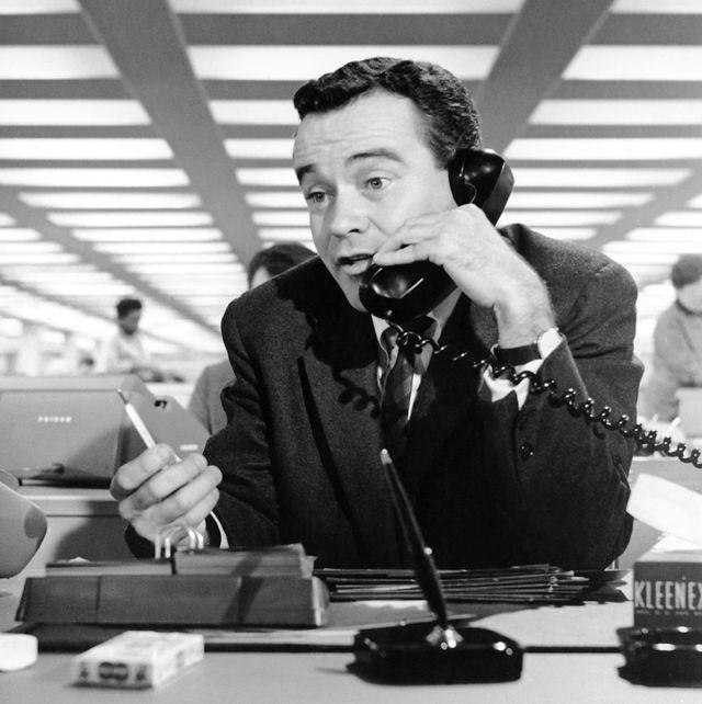 el actor jack lemmon caracterizado como bud baxter en la película el apartamento está al teléfono en una aburrida oficina