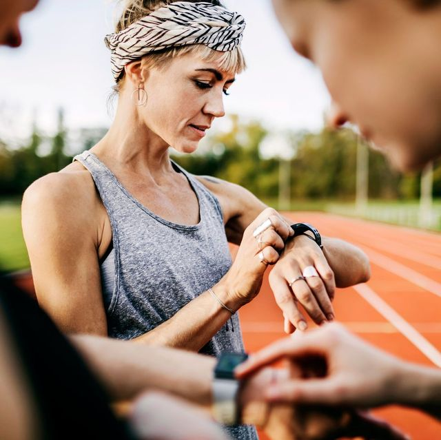 una corredora ajusta su reloj antes de empezar a correr en su entrenamiento para extraer datos útiles sobre su rendimiento