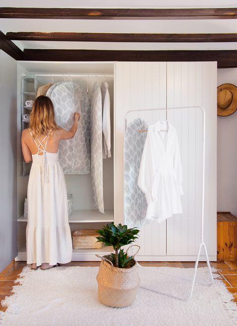 mujer de blanco ordenando un armario con productos compactor