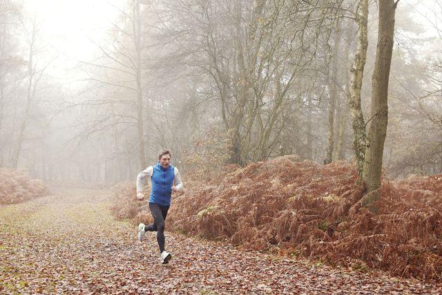 un runner corriendo a través de un bosque otoñal