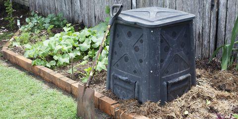 Compost bin in a backyard vegetable garden.