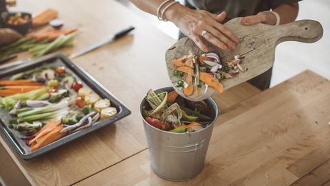scraping vegetable scraps into a compost bucket
