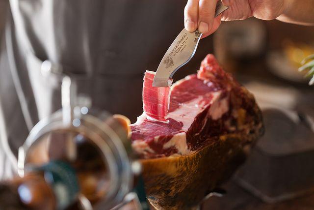 cortador de jamón extrayendo una loncha de ibérico