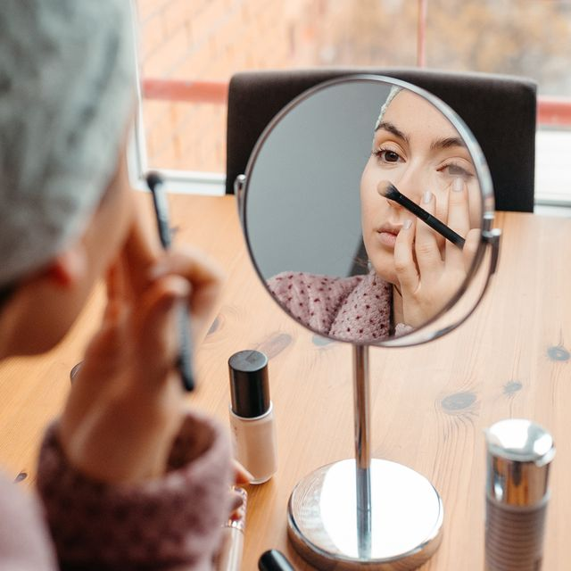 woman applying concealer with brush with magnifying mirror