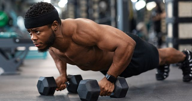 concentrated black guy sportsman pushing up with dumbbells