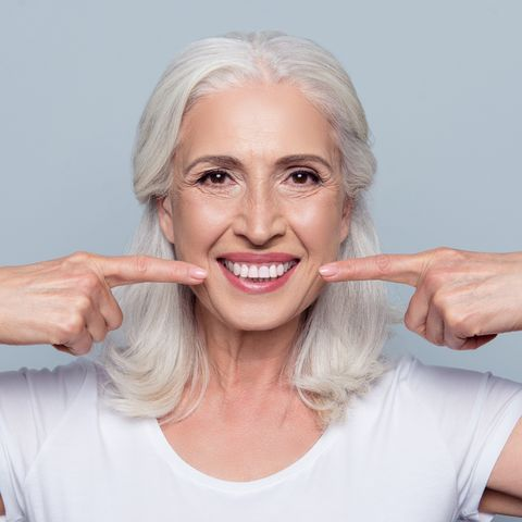 concept of having strong healthy straight white teeth at old age close up portrait of happy with beaming smile female pensioner pointing on her perfect clear white teeth, isolated on gray background
