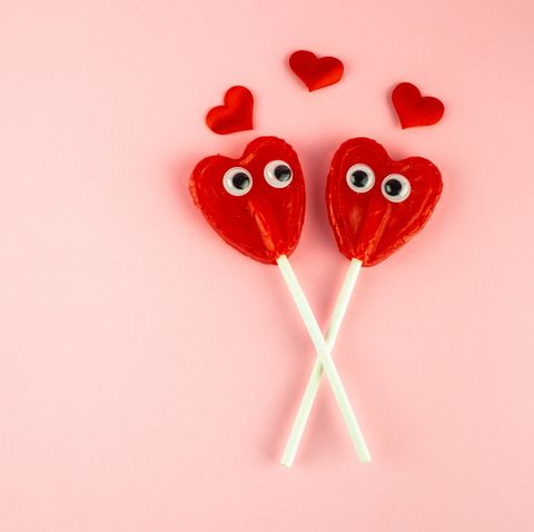 Concept of love and romanticism. Two red heart lollipops with eyes looking at each other and several red hearts
